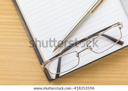 Notebook open blank page and Eyeglasses  on wood table - stock photo
