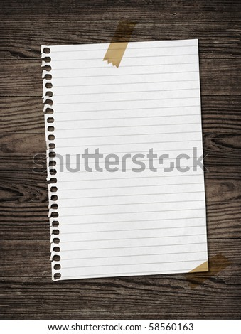 Notebook paper sheet on a wooden table - stock photo