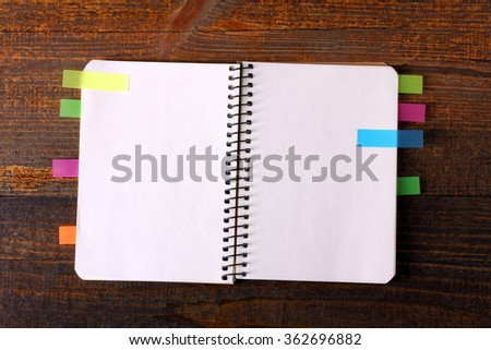 notebook paper with colorful stickers on a wooden Board - stock photo