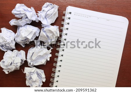 notebook paper with crumpled paper on wooden table - stock photo