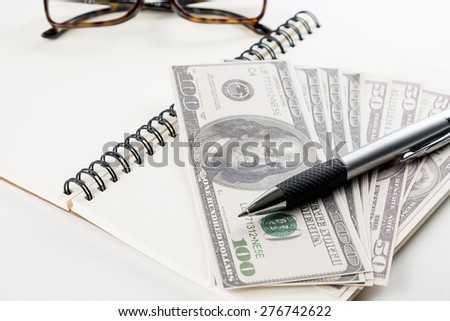 Notebook  pen and money on white background