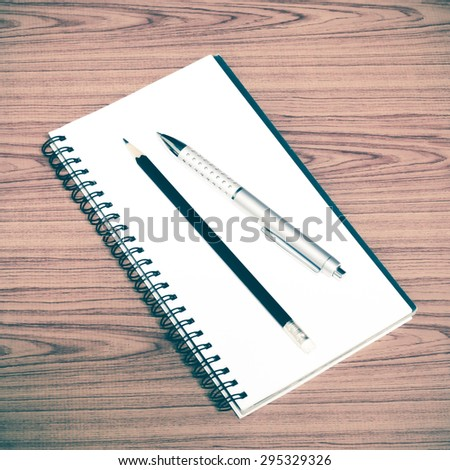 notebook pen and pencil on wood background vintage style