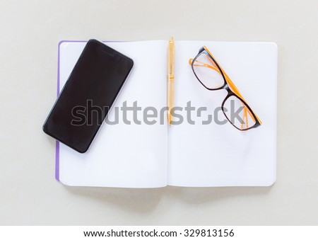 notebook, pen, smart phone and glasses - stock photo