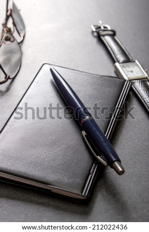 Notebook, pencil and glasses on the table, from above - stock photo