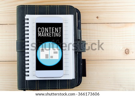 notebook smart phone on wood background word content marketing - stock photo