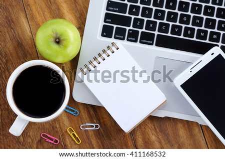 Notebook,smartphone,notepad and a cup of coffee on wooden table - stock photo