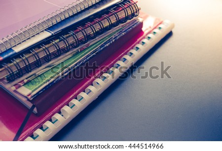 Notebook stack on blackboard background. Back to school concept with space for text. School supplies. Schoolchild and student studies accessories. Back to school concept. Toned image. - stock photo