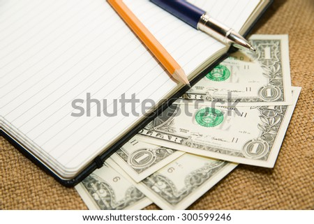 notebook with a blank sheet, pen, pencil and money on the old tissue - stock photo