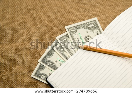 notebook with a blank sheet, pencil and money on the old tissue