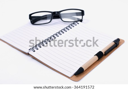 Notebook with a pair of reading black glasses isolated on white background.  - stock photo