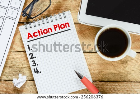 Notebook with action plan. Workplace with keyboard , tablet pc , coffee ,notebook with action plan and pen on wood table - stock photo