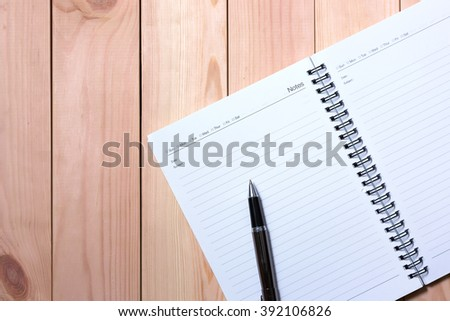 Notebook with Black Pen with wooden pallet background.