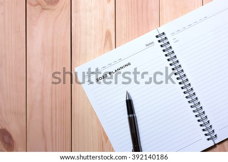 Notebook with Black Pen. Writing 2022 Planning with wooden pallet background.