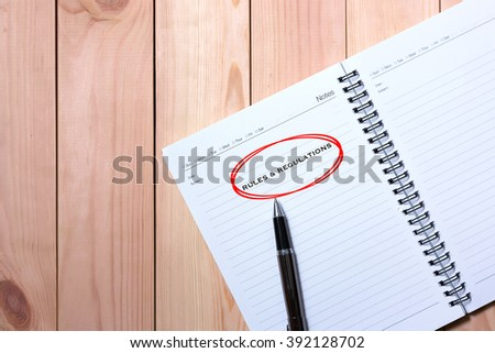 Notebook with Black Pen. Writing Rules and Regulations in Red Circle with wooden pallet background. - stock photo