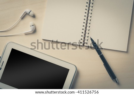 Notebook with blank area for text or message and pen beside small tablet pc and in ear headset on wood table - stock photo