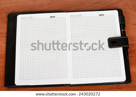 Notebook with blank pages, disclosed and lying on the table, pen