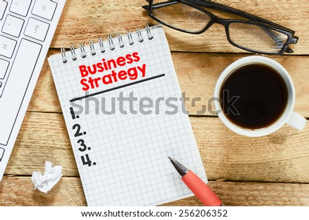 Notebook with business strategy list. Workplace with keyboard , coffee , notebook with business strategy list and pen on wood table - stock photo