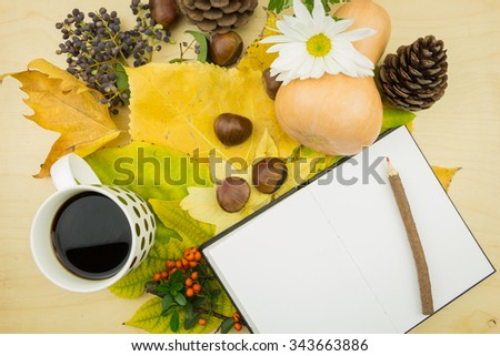 Notebook with cup of coffee and a bouquet of yellow, green autumn leaves,berries and seeds. - stock photo