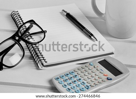 Notebook with eyeglasses and calculator - stock photo