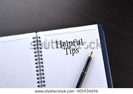 Notebook with fountain pen on wooden table with word Helpful Tips - stock photo