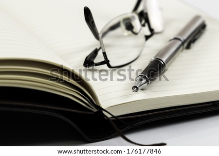 notebook with glasses and pen on table - stock photo