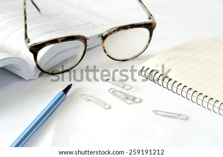 Notebook with glasses and pen on table, close up