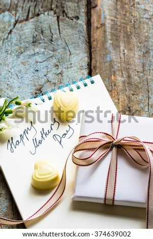 "Notebook with ""happy mothers day"" written, gift box and heart shaped white chocolate candies on a shabby wooden background"