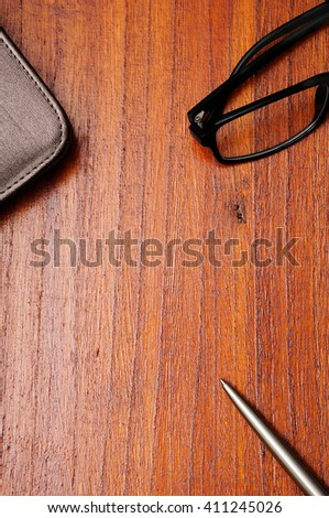 Notebook with leather cover, silver ballpoint pen and glasses on  dark brown wooden background. Copy space in the center from top view - stock photo