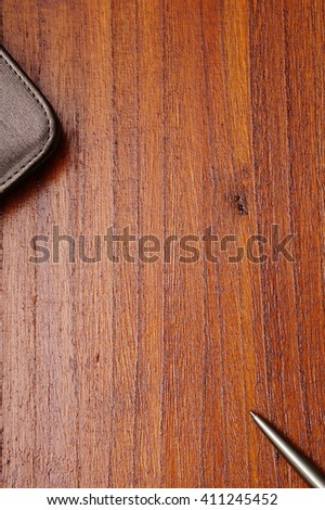 Notebook with leather cover, silver ballpoint pen on  dark brown wooden background. Copy space in the center from top view - stock photo