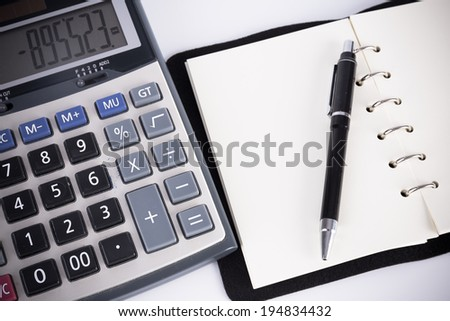 notebook with pen and calculator