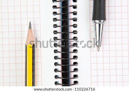 Notebook with pen and pencil, closeup.