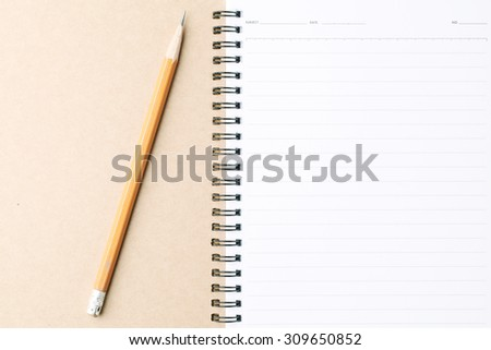 Notebook with pencil on wood background.