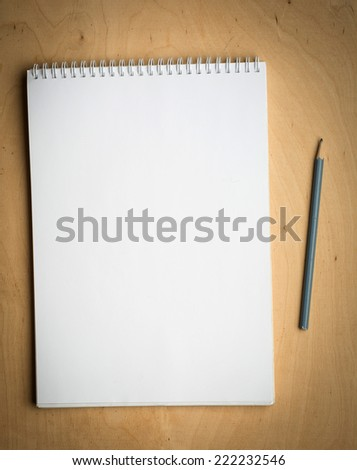 notebook with pencile on a wooden background - stock photo