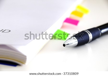notebook with same Pieces of paper and one blue pen - stock photo