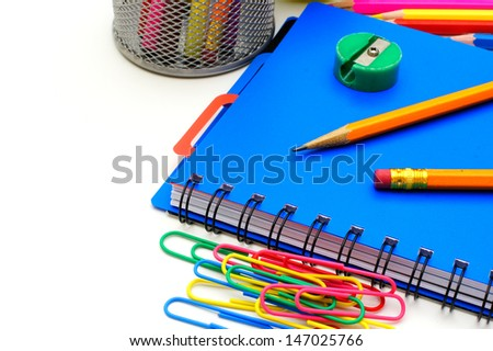 Notebook with school supplies, close up over white
