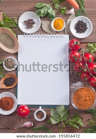notebook with spices and herbs on the old wooden cutting board