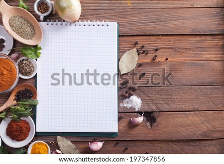 notebook with spices and herbs on the old wooden cutting board - stock photo