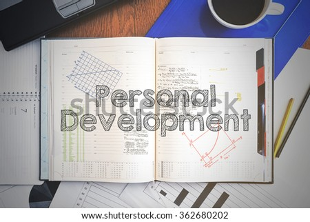 Notebook with text inside associated with the education - personal development . On table are coffee, laptop and some sheet of papers with charts and diagrams - stock photo