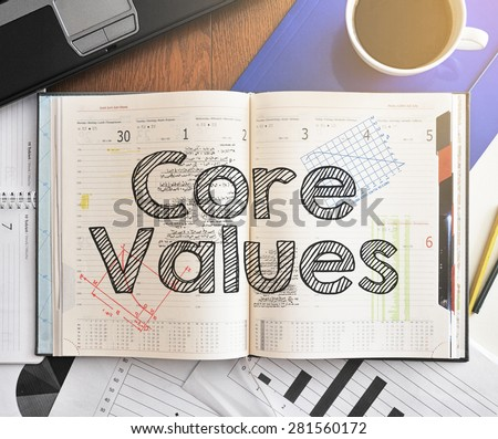Notebook with text inside Core Values on table with coffee, laptop and some sheet of papers with charts and diagrams - stock photo