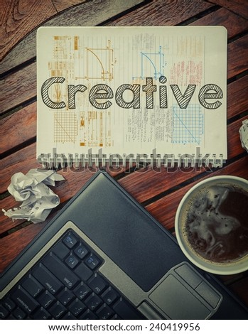 Notebook with text inside Creative on table with coffee, laptop pc and crumpled sheets - stock photo