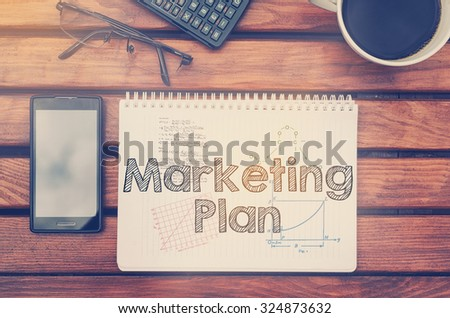 Notebook with text inside Marketing Plan on table with coffee, mobile phone and glasses.