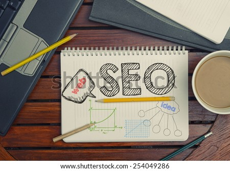 Notebook with text inside SEO on table with coffee, notebook and pencils  - stock photo