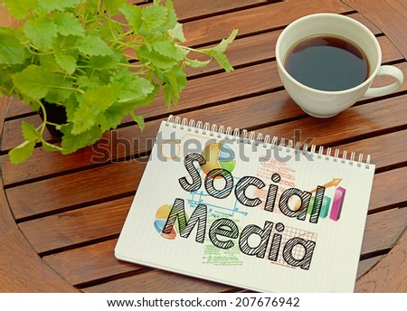Notebook with text inside Social Media on table with coffee and plant. - stock photo
