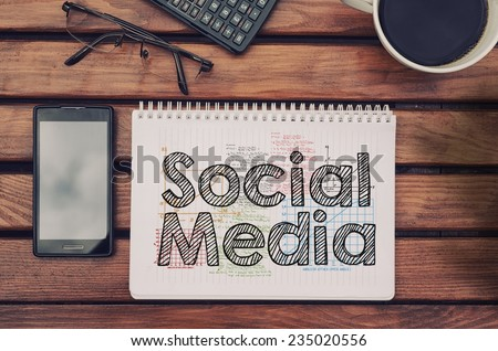 Notebook with text inside Social Media on table with coffee, mobile phone and glasses.  - stock photo
