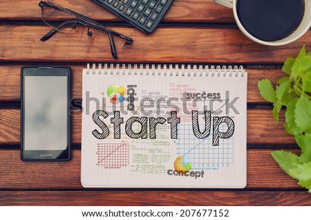 Notebook with text inside Start Up on table with coffee, mobile phone and glasses.  - stock photo