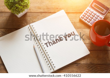 Notebook with text inside Thank you on table with coffee - stock photo