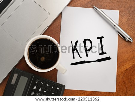 Notebook with text KPI on table with coffee, calculator and notebook  - stock photo