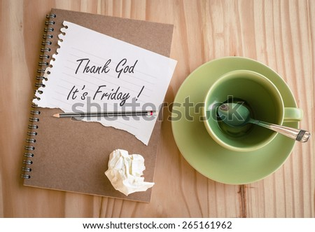 """Notebook with text """"Thank God It's Friday!"""" with empty coffee cup - stock photo"""
