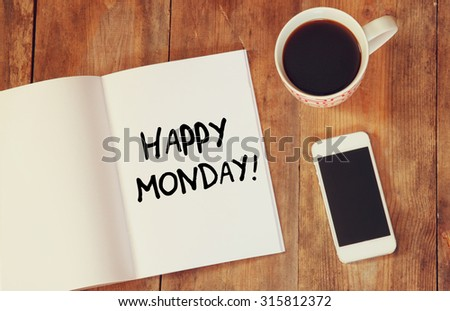 notebook with the phrase happy monday written on it, coffee cup and smart phone. filtered image.  - stock photo
