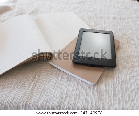 Notebooks and ebook reader on white fabric.
